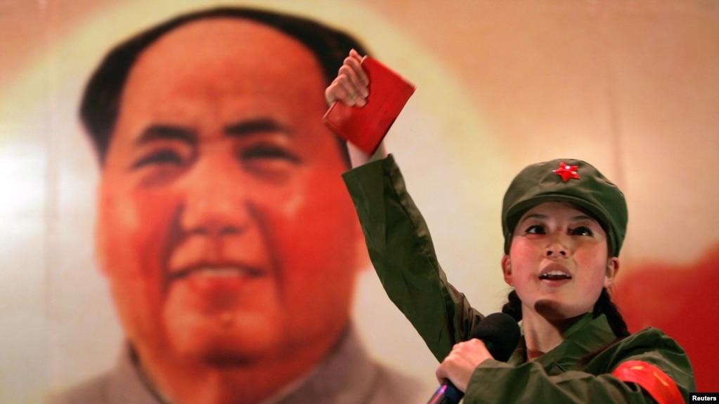 资料照:一名红卫兵手举毛主席语录在毛泽东画像前跳忠字舞