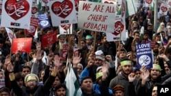"""Những người biểu tình cầm biểu ngữ với hàng """"Ngưng ngay các hành vi xúc phạm tôn giáo""""."""