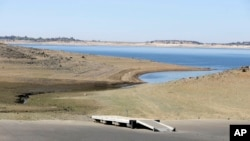 FILE - In this Oct. 6, 2014 file photo, a dock sits high and dry at the end of a boat ramp yards away from the edge of Folsom Lake near Folsom, Calif. (AP Photo/Rich Pedroncelli, File)