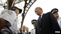 Menteri Dalam Negeri Perancis Brice Hortefeux berbincang-bincang dengan petugas keamanan yang berjaga-jaga di dekat Menara Eiffel di Paris.
