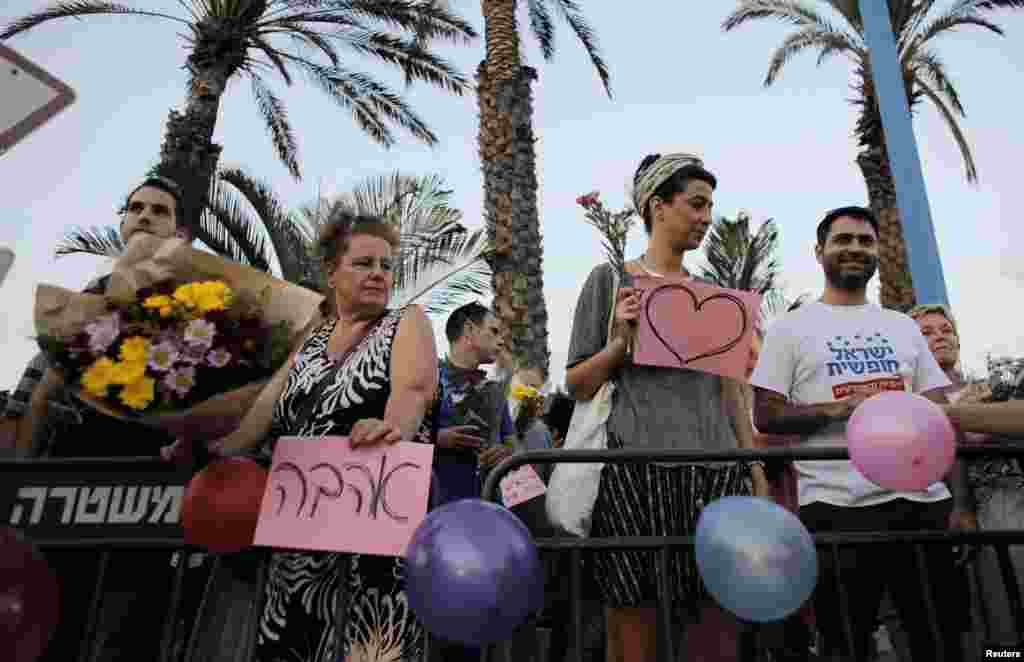 Protesters hold signs in support of the wedding outside the wedding hall in Rishon Lezion, Aug. 17, 2014.