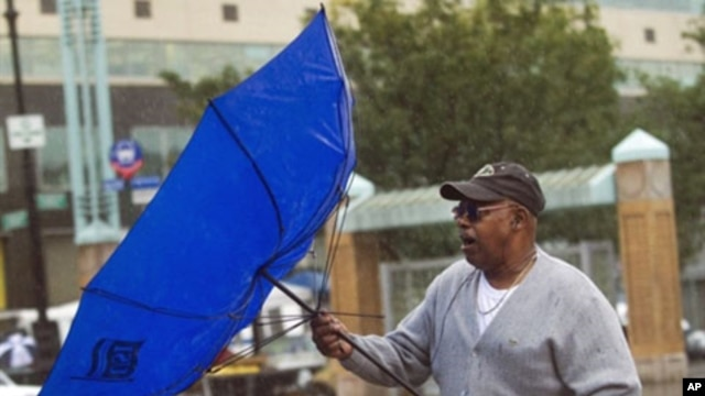 A commuter struggles with his umbrella during heavy rain in the Bronx borough of New York City, 01 Oct 2010