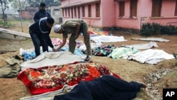 An Indian official inspects bodies covered by blankets in West Midnapore district's Sildha, West Bengal state, 16 Feb 2010