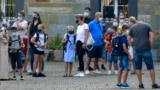 FILE - In this Wednesday, Aug. 12, 2020 file photo, parents wait with children on the schoolyard for the start of their first day at a school in Gelsenkirchen, Germany. (AP Photo/Martin Meissner, File)