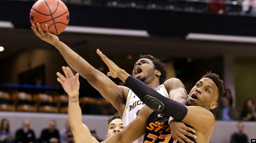 University of Michigan guard Derrick Walton Jr. (10) is fouled as he shoots by Oklahoma State University forward Leyton Hammonds (23) during a first-round game in the men's NCAA college basketball tournament in Indianapolis, Indiana, March 17, 2017.
