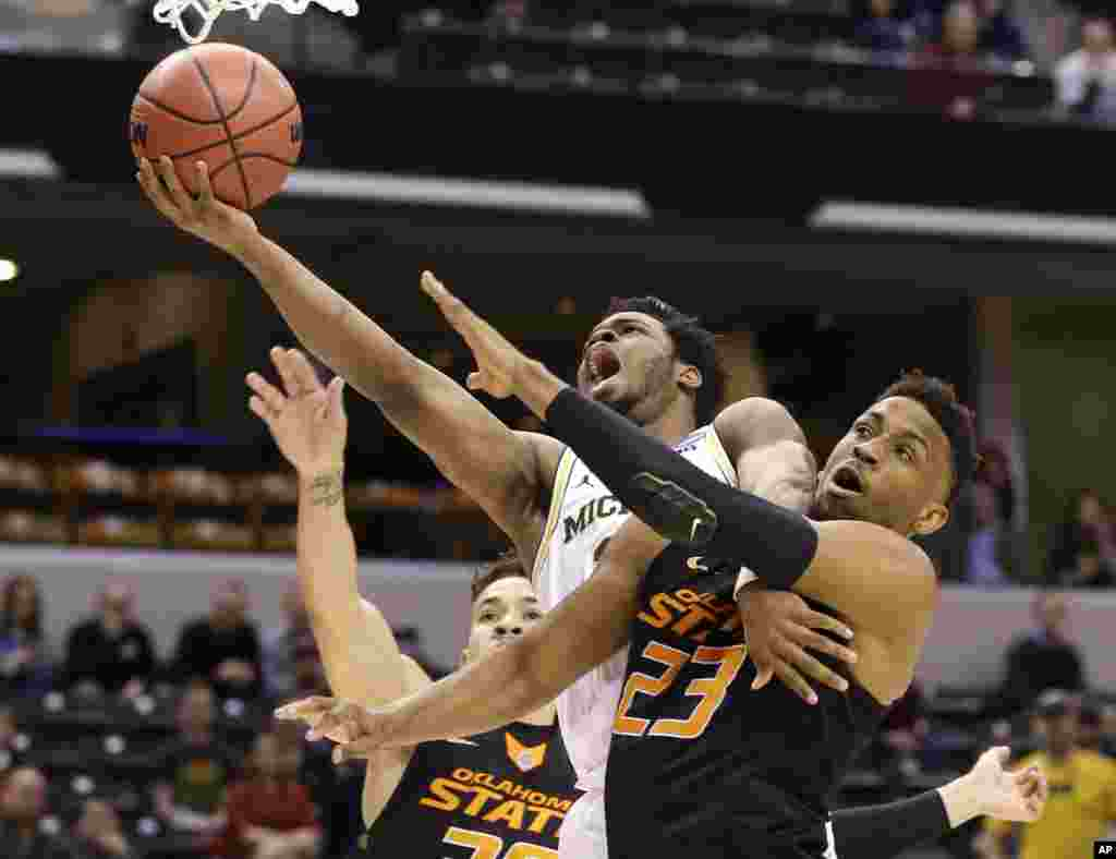 University of Michigan guard Derrick Walton Jr. (10) is fouled as he shoots by Oklahoma State University forward Leyton Hammonds (23) during a first-round game in the men's NCAA college basketball tournament in Indianapolis, Indiana.
