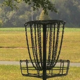 Instead of shooting for a hole on the green, disc golf players aim for a raised metal basket.