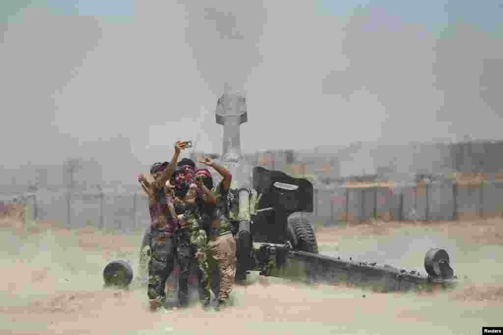 Shi'ite fighters take a selfie while firing artillery towards Islamic State militants near Falluja, Iraq.