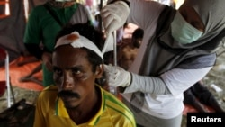A migrant, who arrived in Indonesia by boat yesterday along with other Bangladeshi and Rohingya migrants, receives medical treatment in Kuala Langsa, in Indonesia's Aceh province, May 16, 2015.