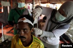 A migrant, who arrived in Indonesia by boat Friday along with other Bangladeshi and Rohingya migrants, receives medical treatment in Kuala Langsa, in Indonesia's Aceh province, May 16, 2015.