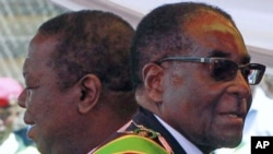Zimbabwean President Robert Mugabe (R) and Prime Minister Morgan Tsvangirai arrive at a rally marking Zimbabwe's 31st independence anniversary celebrations in Harare, Zimbabwe, April 2011. (file photo)