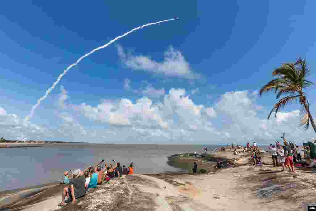 មនុស្សម្នាថតរូបរ៉ូកែតអវកាស Ariane 5 ដែលមានផ្ទុកផ្កាយរណប Galileo ចំនួនបួនពីស្ថានីយអវកាស ESA European Spaceport ក្នុងក្រុង Kourou កោះ French Guiana។