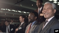 FILE - President Nelson Mandela, right, flanked by Cyril Ramaphosa, second from right, smiles at the World Trade Centre near Johannesburg.