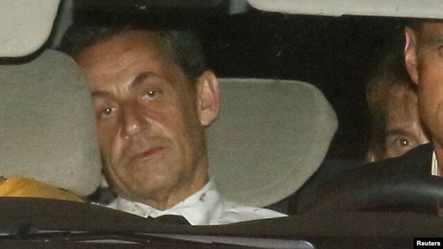 Former French President Nicolas Sarkozy arrives with police by car at the financial investigation unit in Paris to be presented to a judge late July 1, 2014.