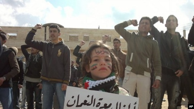 "Demonstrators protest against Syria's President Bashar Al-Assad in Marat al-Numan near the northern province of Idlib. The bannr reads, ""The children Marar Al-Numan, sacrifice our lives for you Bab Amro"", March 2, 2012."