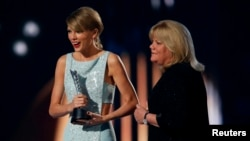 Taylor Swift accepts the Milestone Award from her mother, Andrea, at the 50th Annual Academy of Country Music Awards in Arlington, Texas, April 19, 2015.