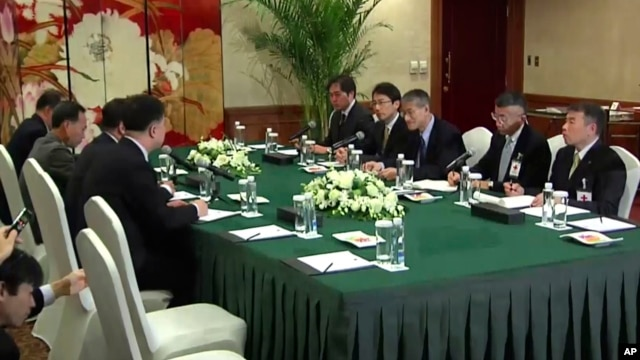 Video image shows Osamu Tasaka (3rd-R), director general of the International Department at the Japanese Red Cross, meeting with Ri Ho Rim (3rd-L), secretary general of North Korea's Red Cross Society, in Shenyang, China, March 3, 2014.
