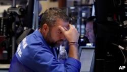 Pialang Kevin Lodewick di lantai Bursa Saham New York, Jumat (21/8).