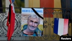 A portrait of mountain guide Frenchman Herve Gourdel hangs near a French flag outside the town hall in Saint-Martin-Vesubie, Sept. 25, 2014.