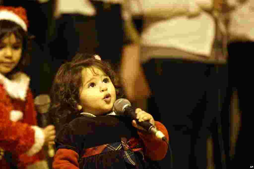 Seorang anak perempuan Kristen Mesir ikut menyanyi dalam misa Tahun Baru di gereja Katedral Cave (Santo Simon) di distrik Moqattam, Kairo, Mesir (31/12).