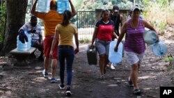 13일 베네수엘라 수도 카라카스에서 정전으로 인해 식수 공급이 중단되자 주민들이 물통을 들고 이동하고 있다.