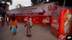 Passants devant une banderoles de la Première ministre bangladaise Sheikh Hasina près du temple Dhakeshwari à Dhaka, 1er janvier 2019. (Photo AP/Anupam Nath)
