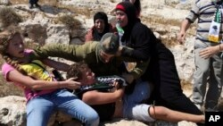 "FILE - Nariman Tamimi and her daughter Ahed try to free her son Mohammed from an Israeli soldier during a protest near the West Bank village of Nebi Saleh, Aug, 28, 2015. Israeli Cabinet ministers have proposed legislation that seeks to outlaw photographing Israeli soldiers ""for the sake of shaming them,"" a ban rights groups say would amount to government censorship."