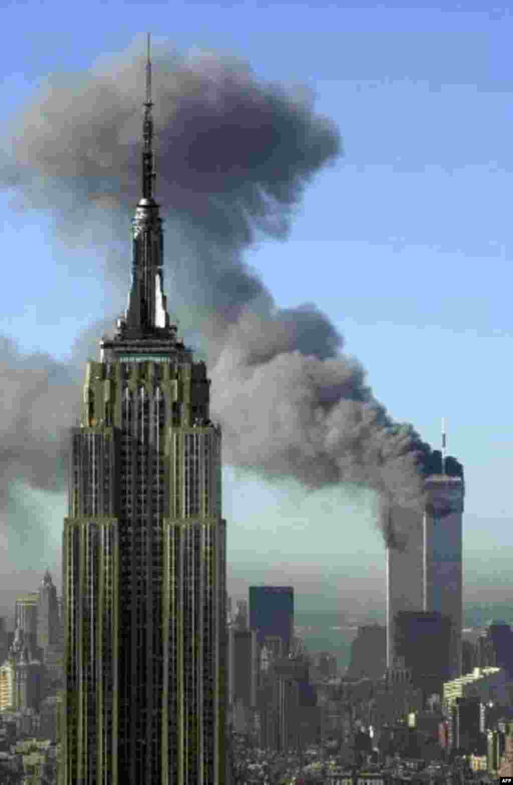 Plumes of smoke pour from the World Trade Center buildings in New York Tuesday, Sept. 11, 2001. Planes crashed into the upper floors of both World Trade Center towers minutes apart Tuesday in a horrific scene of explosions and fires that lead to the colla