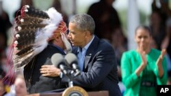 President Barack Obama with first lady Michelle Obama, Standing Rock Sioux Tribal Nation Chairman Dave Archambault II, in Cannon Ball, N.D., Friday, June 13, 2014, during a Cannon Ball flag day celebration, at the Cannon Ball powwow grounds.