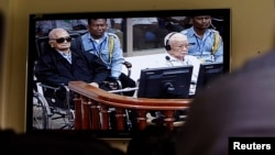 FILE - Khieu Samphan (2-L), former Khmer Rouge head of state, and Noun Chea (L), who was the Khmer Rouge's chief ideologist and No. 2 leader, are seen on a screen at the court's press center of the U.N.-backed war crimes tribunal in Phnom Penh, Cambodia, Aug. 7, 2014.