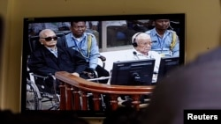 FILE - Khieu Samphan, second from right, former Khmer Rouge head of state, and Noun Chea, left, who was the Khmer Rouge's chief ideologist and No. 2 leader, are seen on a screen at the court's press center of the U.N.-backed war crimes tribunal in Phnom Penh, Cambodia, Aug. 7, 2014.