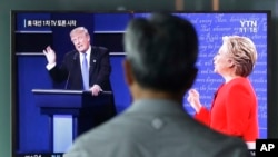 A man watches a TV screen showing the live broadcast of the U.S. presidential debate between Democratic presidential candidate Hillary Clinton and Republican presidential candidate Donald Trump, at Seoul Railway Station in Seoul, South Korea, Sept. 27, 20