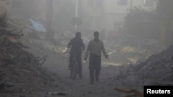 Men are seen inspecting damage that was reportedly caused by shelling from Syrian government forces, along a street in the Duma neighborhood of Damascus, Nov. 17, 2013.