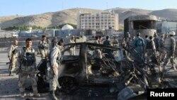 Petugas keamanan Afghanistan meriksa kendaraan yang rusak yang digunakan dalam serangan bom bunuh diri di luar konsulat AS di Herat (13//2013)