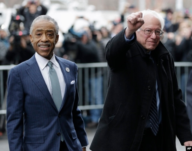 Democratic presidential candidate Sen. Bernie Sanders, I-Vt., right, accompanied by Rev. Al Sharpton, raises a fist as he arrives for a breakfast meeting at Sylvia's Restaurant, Feb. 10, 2016, in the Harlem neighborhood of New York.