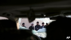 Afghan civilians watch over site of Friday's suicide attack, shooting in Kabul, Jan. 18, 2014.
