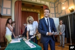 French President Emmanuel Macron and his wife Brigitte Macron pick up ballots before voting in the first round of the two-stage legislative elections in Le Touquet, northern France, June 11, 2017.