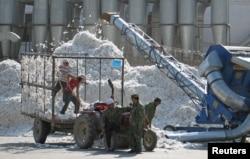 2005年 10月,新疆石河子生产建设兵团的一个棉花加工厂的工人们在工作。(资料照片)