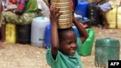 Une jeune garçon porte de l'eau dans un camp de déplacés à 180 km de Maputo, le 16 mars 2000.