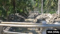 Alat berat ekskavator membersihkan aliran sungai mati di desa Poi yang dipenuhi material pasir bercampur batu-batu besar yang terbawa banjir bandang, 9 Desember 2019. (Foto: Yoanes Litha/VOA)