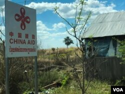 "A land transporting truck attached with ""China Aid"" placard at the the construction site of a new Cambodian-China friendship hospital in Tboung Khmum province, in March 2019 (Sun Narin/VOA Khmer)"