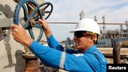 Basra rafinerisinde bir petrol boru valfini kontrol eder işçi, Basra, 1 Mart 2014.