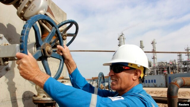FILE - A worker checks the valve of an oil pipe at Basra refinery in Basra province, March 1, 2014.