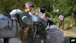 Naoružani pripadnici proruskih separatističkih snaga na kontrolnom punktu izvan Slavjanska, u istočnoj Ukrajini