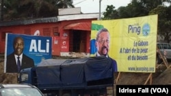 FILE - The election campaign posters of incumbent Gabonese President Ali Bongo and his rival Jean Ping of the opposition are side by side in Libreville, Aug. 26, 2016.