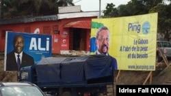 Les affiches de la campagne électorale du président gabonais sortant Ali Bongo et de son rival Jean Ping de l'opposition, sont côte-à-côte, à Libreville, 26 août 2016. (VOA/Idriss Fall)