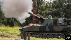 FILE - In this Taiwan Military News Agency photo, a Taiwan artillery gun fires a live round during exercises in Taichung, Taiwan, Sept. 16, 2021. U.S. defense officials are refusing to confirm reports that American forces are in Taiwan, secretly training Taiwanese troops.