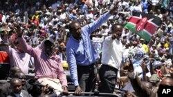 Kenya's former Education Minister William Ruto, center left, Kenya's Deputy Prime Minister Uhuru Kenyatta, center, and Kenya's Vice President Kalonzo Musyoka, center right, wave to thousands of people during a prayer rally at Uhuru Park, Kenya, Monday, Ap