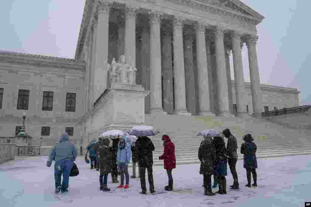 گروهی از گردشگران در هوای برفی خود را به مقابل ساختمان دیوان عالی آمریکا رسانده اند. برف و توفان روز چهارشنبه موجب تعطیلی مدارس و ادارات دولتی در پایتخت آمریکا شد.
