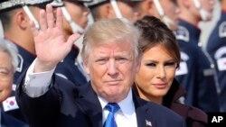 Predsednik SAD Donald Tramp maše, dok prva dama Melanija Tramp stoji pokraj njega, nakon dolaska u vojnu bazu Osan u Pjeongtaeku, Južna Koreja, 7. novembra 2017.